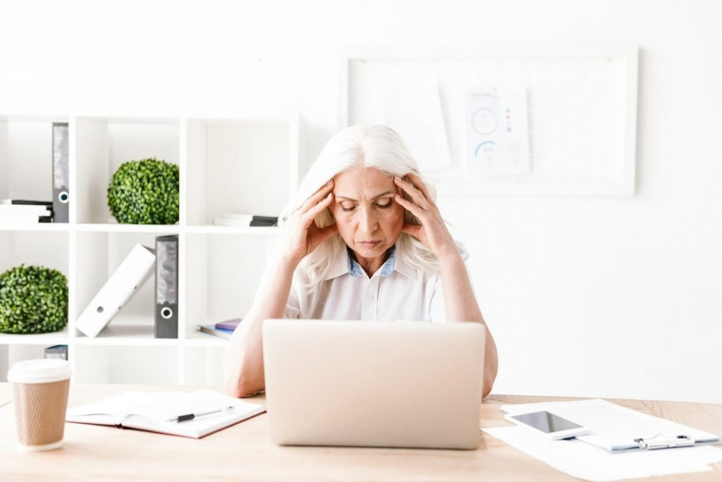 Confused mature woman using laptop computer.
